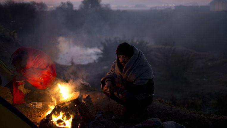 Een migrant in de Noord-Griekse grensplaats Idomeni. Beeld ap