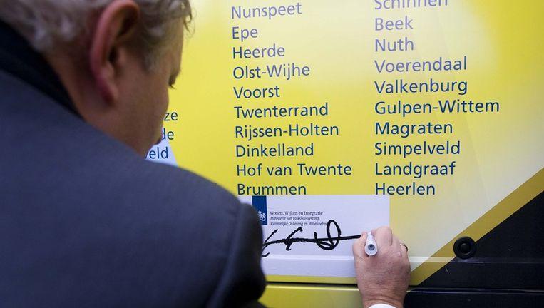 Toenmalig minister Eberhard van der Laan van Wonen, Wijken en Integratie zet zijn handtekening op een bus die diverse (krimp-)regio's aandoet, en bekrachtigt daarmee het zogeheten Interbestuurlijke Actieplan Bevolkingsdaling. Beeld