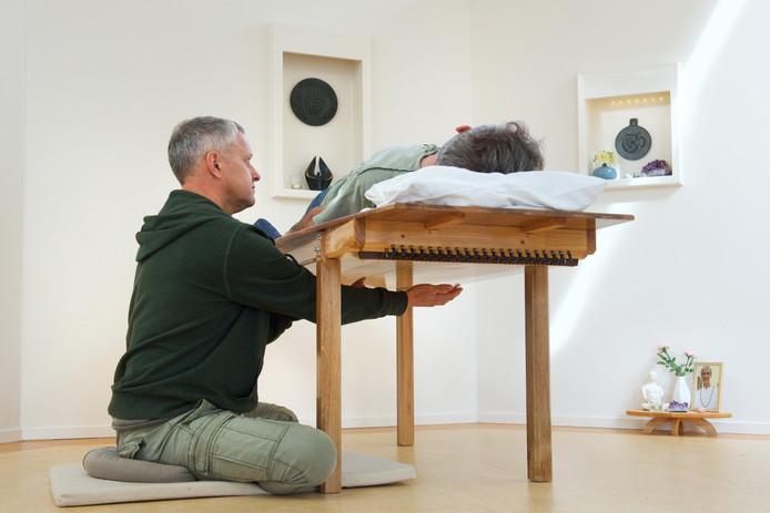 Martien Hontelez met zijn zelfgemaakte klanktafel, een soort massagetafel (van hout) waaronder snaren zitten. De therapeut brengt de snaren in trilling. Op de tafel ligt de cliënt.
