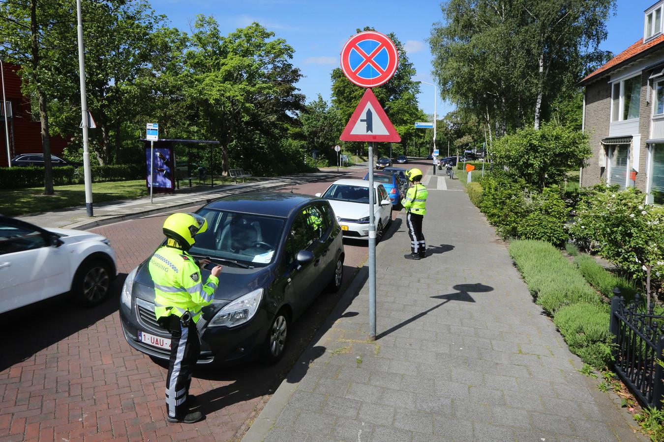 Foutparkeerders worden aan de Langendijk in Breda op de bon geslingerd.