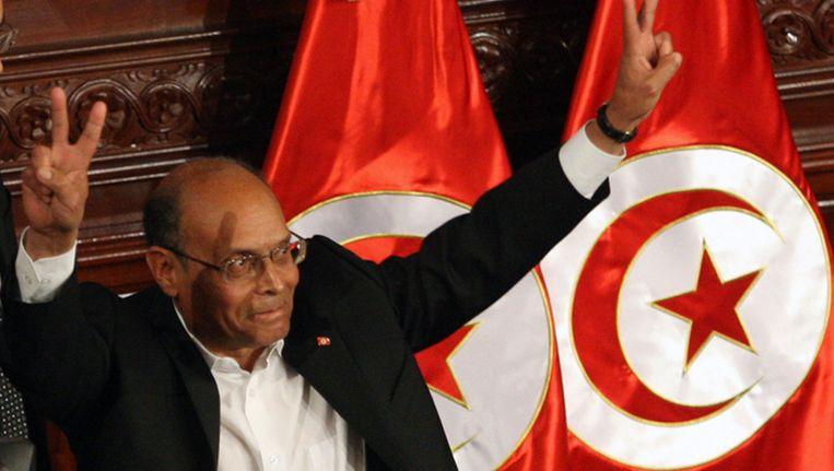 De Tunesische president Moncef Marzouki maakt het vredesteken na het tekenen van de nieuwe grondwet. Beeld ap