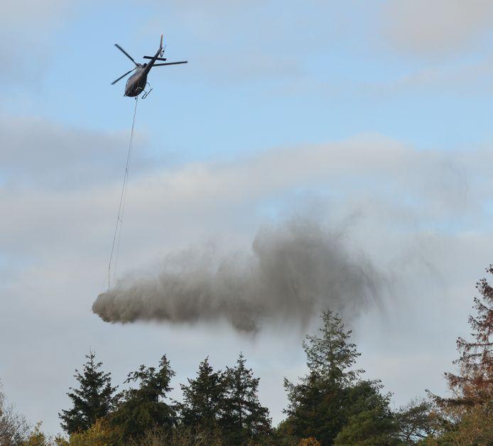 Steengruis wordt vanuit een helikopter uitgestrooid boven de bossen.