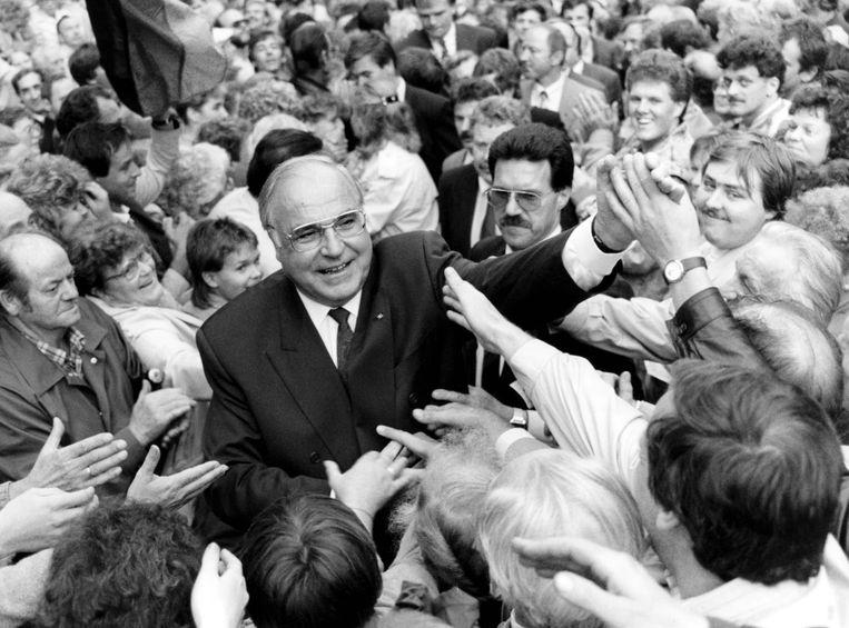 Helmut Kohl wordt toegejuicht door duizenden Oost-Duitsers  in 1990.  Beeld AFP