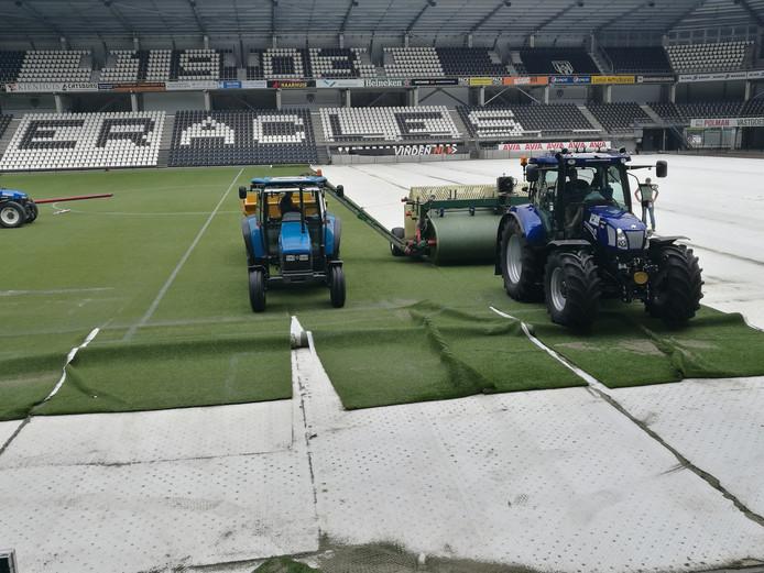 Nieuwe stroken kunstgras voor het veld in het Polman Stadion van Heracles. De club ligt dwars als het gaat om de terugkeer naar natuurgras in de complete eredivisie.
