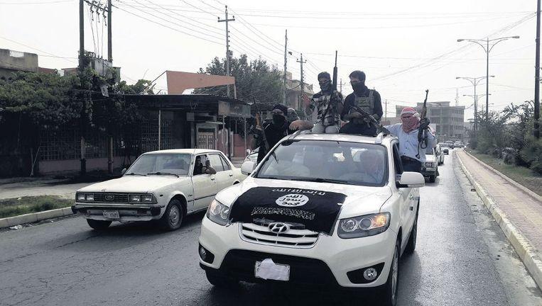 Strijders van Isis rijden in Mosoel in auto's van de Iraakse veiligheidstroepen die ze buit hebben gemaakt bij de inname van de stad. Beeld reuters