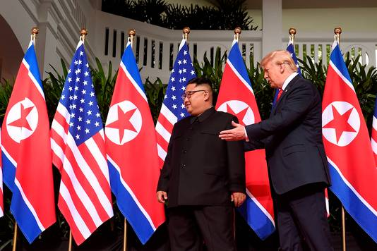 Trump wijst Kim de weg, een hand op zijn rug.