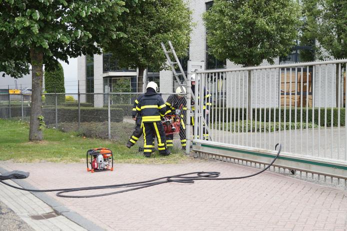 De brandweer zaagde een gat in het hek om bij de brand te komen.