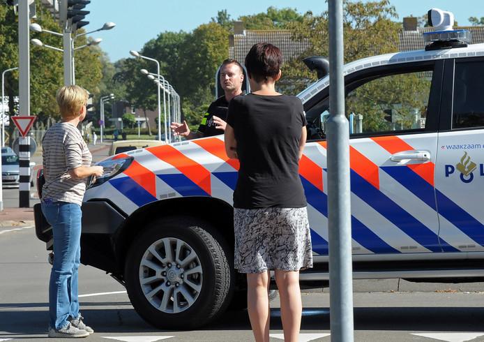 Een agent staat ouders te woord bij de ingang van De Rede.