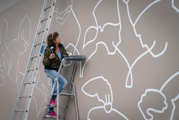 Denny Baggen tekent oude ambachten op de muur van de voormalige technische school in Arnhem.