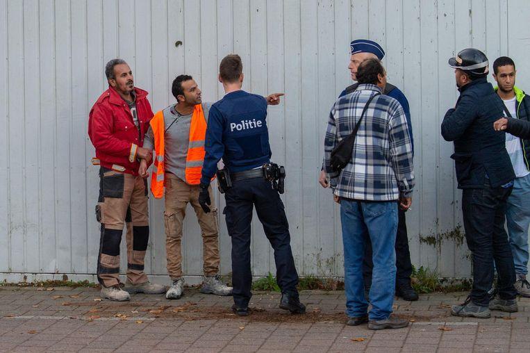Ook op de begane grond raken de gemoederen soms even verhit. De politie probeert de arbeiders te kalmeren.