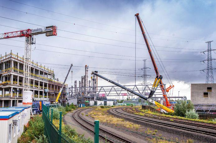 De kranen plaatsten de dubbeldeksbrug over de spoorweg. Die moet vanaf de zomer van 2021 werknemers van de nieuwbouw van DP World links naar de parking rechts brengen.