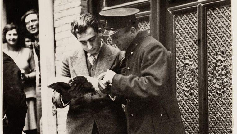 Amsterdam 1930: er is een auto te water geraakt; in de telefoongids wordt het nummer van de hulpdiensten opgezocht. Beeld Stadsarchief Amsterdam