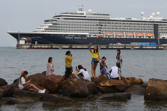 Toeristen maken selfies bij het cruiseschip van de Holland America Line.