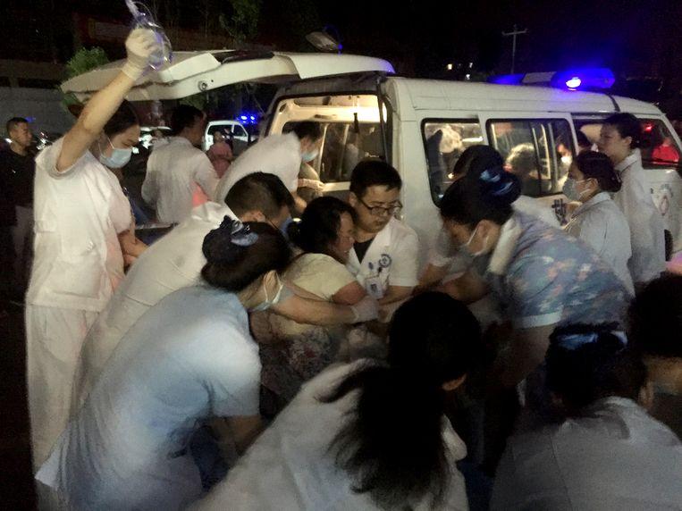 Een gewonde vrouw wordt geholpen in Yibin in de zuidwestelijke Chinese provincie Sichuan, na de aardbeving.