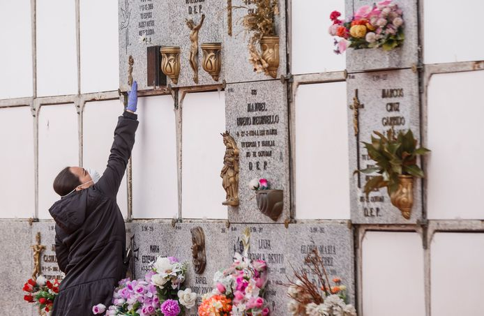 Une femme portant un masque et des gants lors de l'enterrement d'un homme décédé du Covid-19 à Madrid, le 23 mars 2020