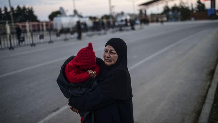 Een Syrische vluchteling wacht met haar kleinkind bij de grens met Turkije. Ze is gevlucht voor Russische luchtaanvallen. Beeld afp