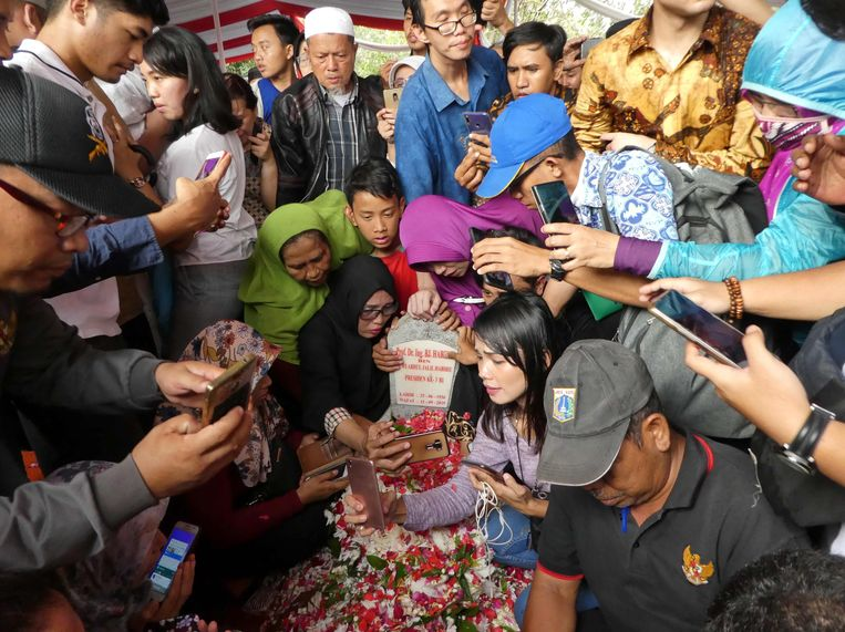 Rouwende Indonesiërs maken na afloop van de begrafenisceremonie selfies bij het graf van oud-president  B.J. Habibie, die op 11 september inJakarta overleed. Habibie was minister en vice-president en was in 1998 en 1999 de derde president van Indonesië, als opvolger van Soeharto.   Beeld AFP