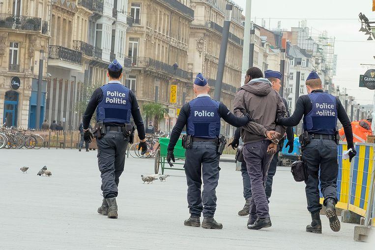 De politie pakt iemand op in voetgangerszone die het samenscholingsverbod niet naleefde.