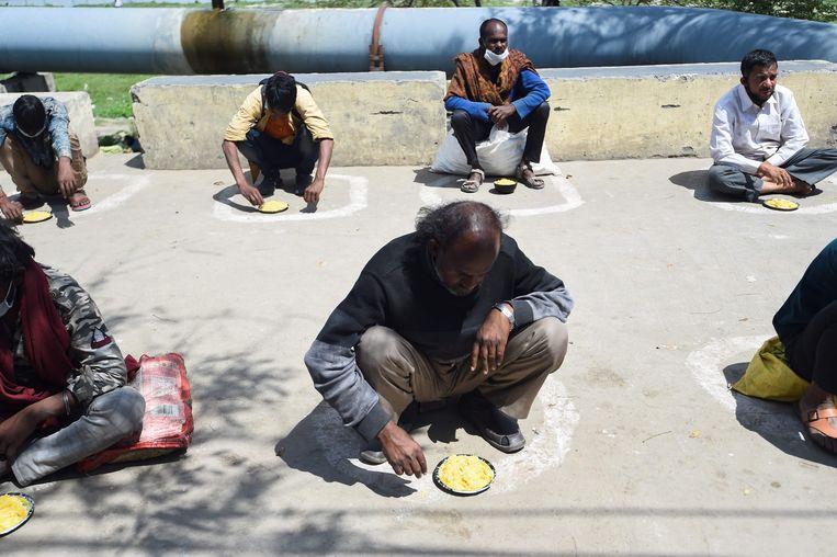 Overal zie je cirkels op de grond in India, die ervoor moeten zorgen dat mensen afstand van elkaar houden. Hier krijgen enkele dakloze mensen in hun eigen cirkeltjes wat te eten.
