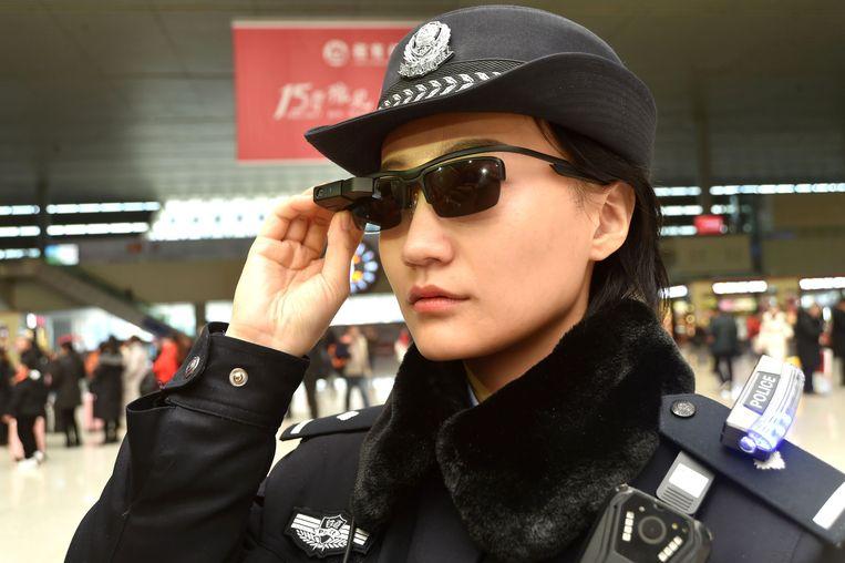 Een Chinese politieagente test de bril uit in het drukke treinstation van Zhengzhou.
