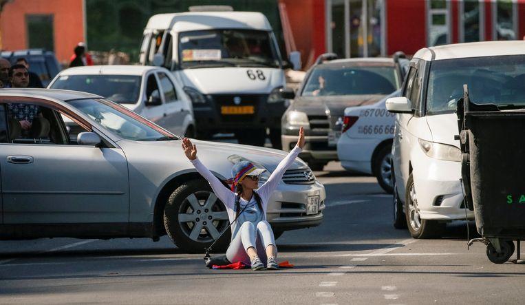 Een manifestante blokeert het verkeer in de hoofdstad Jerevan.