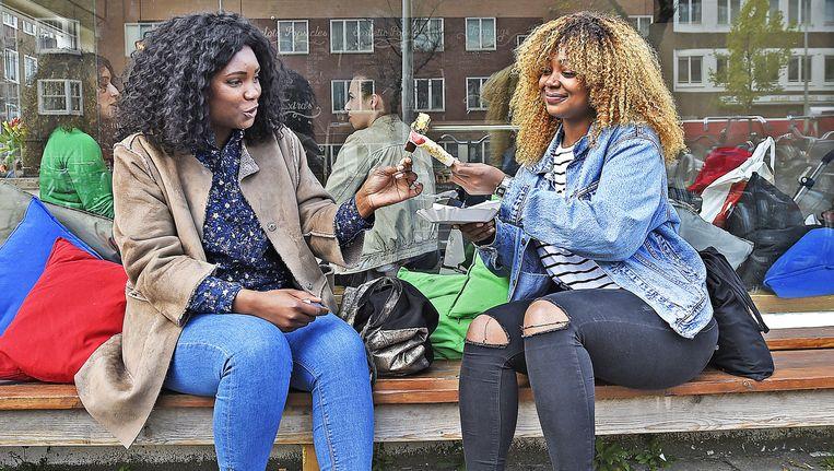 Twee vrouwen vergelijken de handgemaakte ijsjes van de IJslollywinkel in Amsterdam-West. Beeld Guus Dubbelman/de Volkskrant