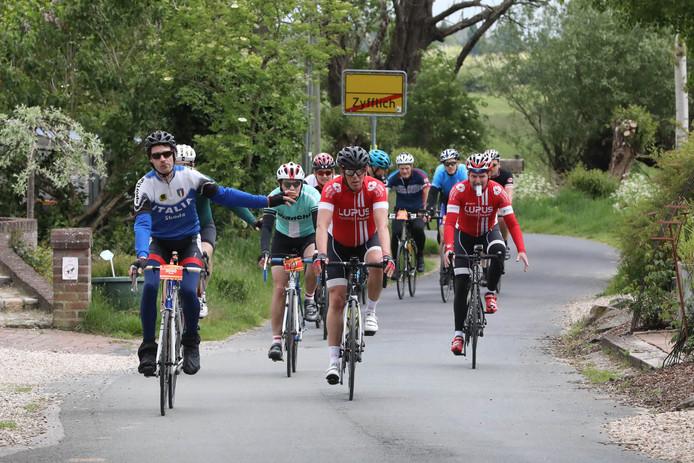 Een groep wielrenners passeert het Duitse dorp Zyfflich tijdens de Ronde van Nijmegen.
