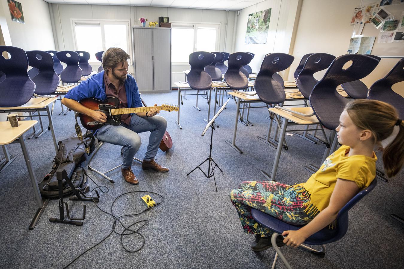 Gitaardocent Willem Ouwehand van Kaliber Kunstenschool laat de negenjarige Merle Teunis uit Wierden horen wat ze allemaal kan leren.