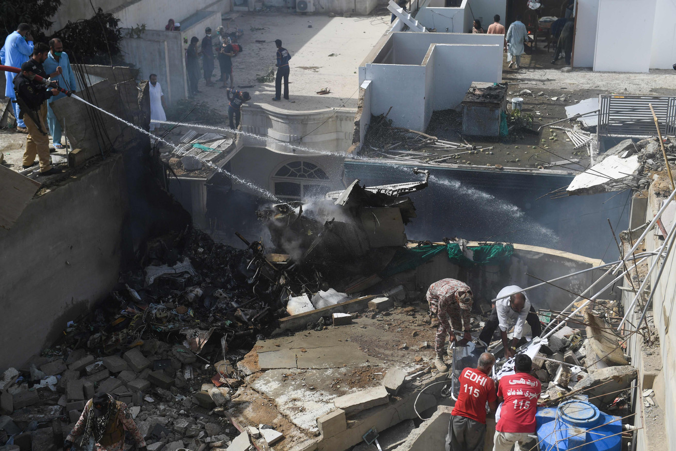 Reddingswerkers en politie blussen een brokstuk op de rampplek met water.