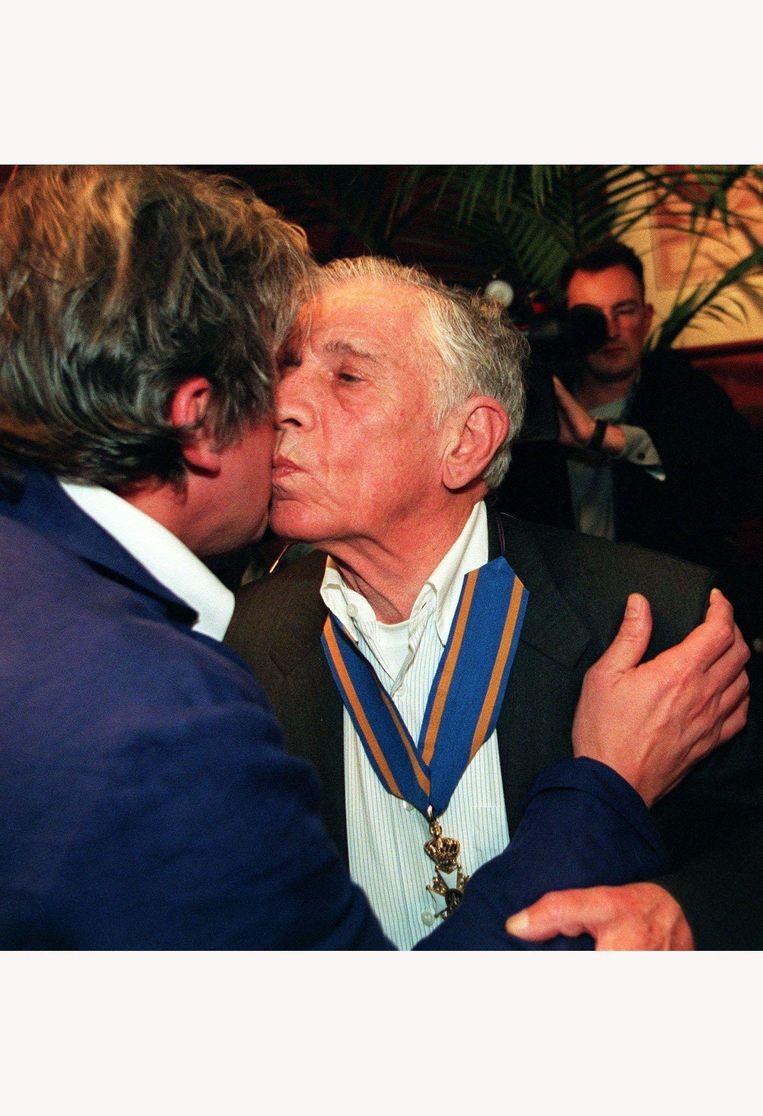 Joop Schafthuizen, de vriend van Gerard Reve, feliciteert de schrijver in 1998 met de onderscheiding van Commandeur in de Orde van de Nederlandse Leeuw. Beeld anp