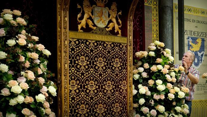 en man zet bloemen neer in de Ridderzaal een dag voor Prinsjesdag. Traditiegetrouw wordt hier op de derde dinsdag van september de troonrede uitgesproken door Koningin Beatrix