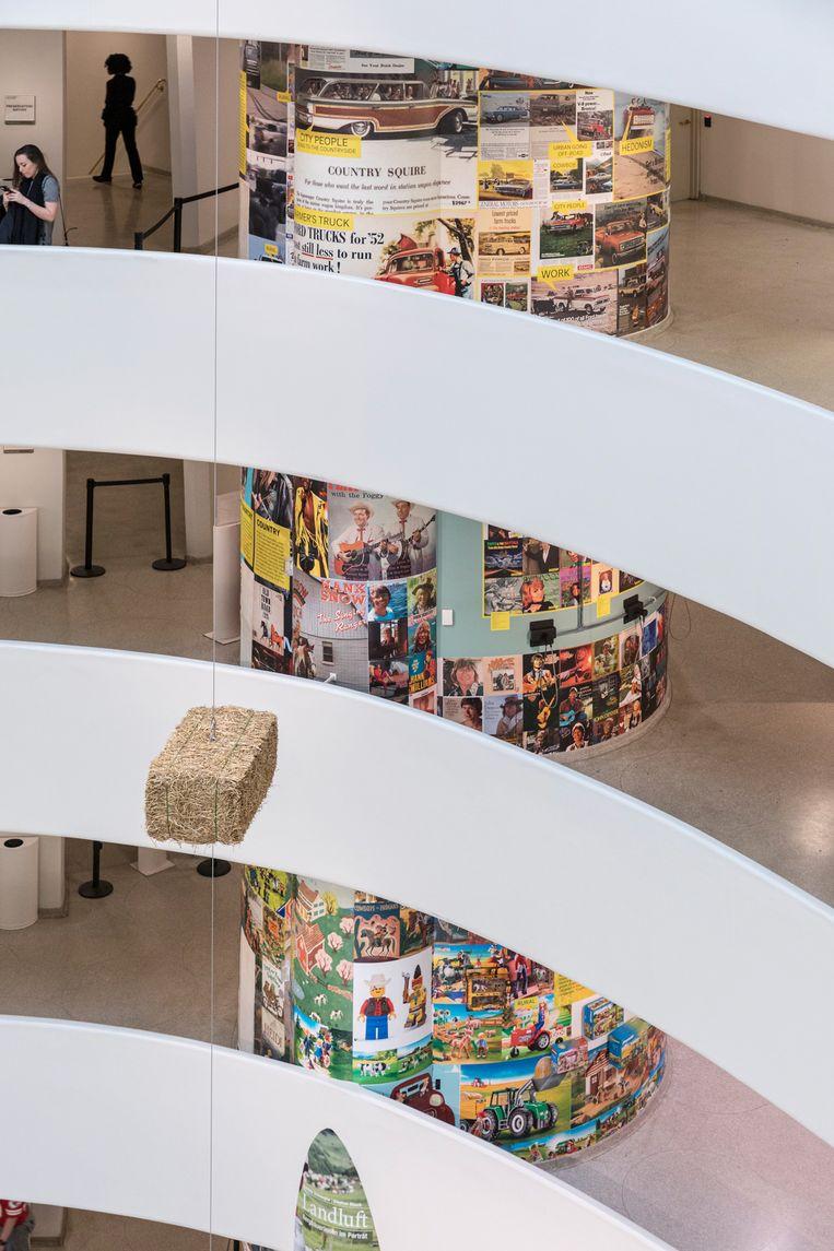 Een dikke zuil is volgeplakt met tijdschriftcovers en speelgoedverpakkingen die clichés over het platteland en de stad tonen in Countryside, The Future in het Guggenheim Museum in New York.  Beeld Laurian Ghinitoiu