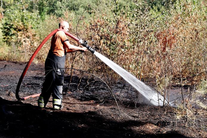 Een brandweerman blust het vuur na.