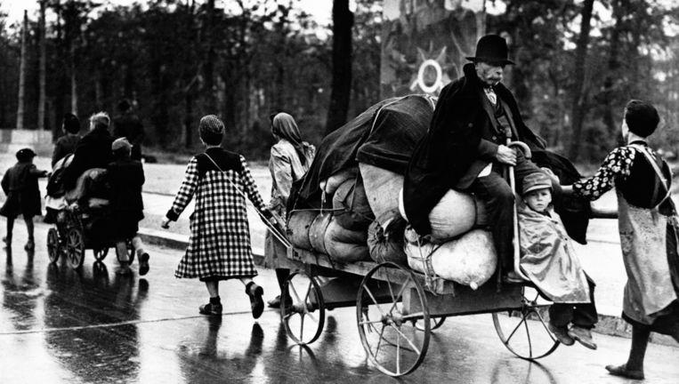 Duitsers op weg naar Berlijn na de nederlaag in 1945. Op de achtergrond een Sovjet-poster.y Beeld Getty