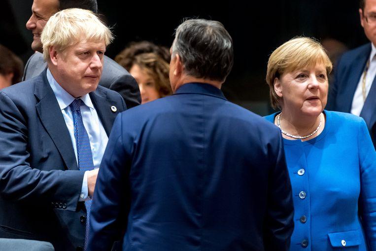 De Britse premier Boris Johnson met Duits bondskanselier Angela Merkel, gisteren op de Europese top in Brussel.