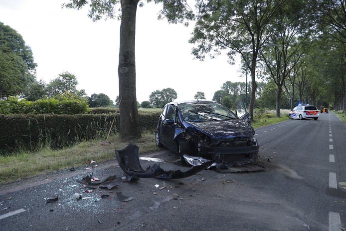 De Laageindsedijk in Rijkevoort ligt bezaaid met brokstukken nadat de auto over de kop was geslagen.