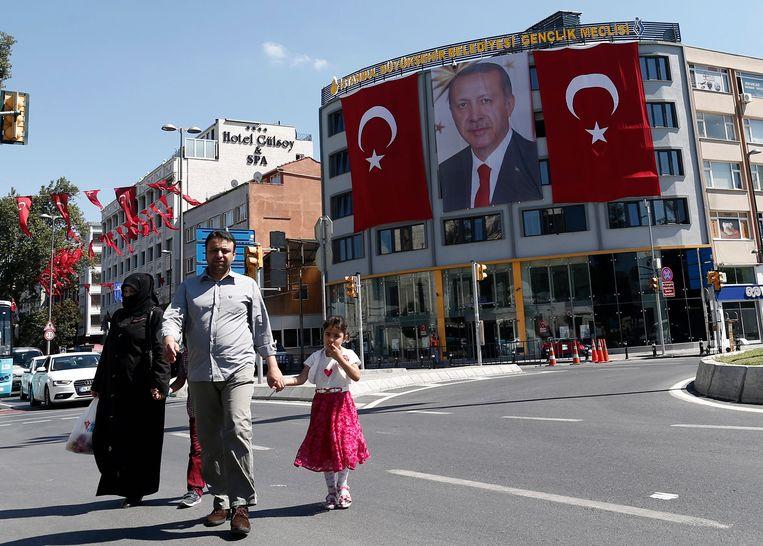 Toeristen lopen voorbij een foto van de Turkse president Recep Tayyip Erdogan in Istanbul. Beeld epa