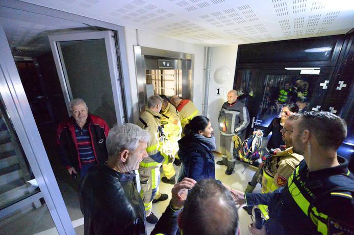 Tulay Sarikaia (midden) is opgelucht, nadat ze door de brandweer is bevrijd uit een lift. Door een stroomstoring was ze vast komen te zitten aan de Apeldoornse Normastraat. Brandweerlieden bekommeren zich op de achtergrond nog over de lift.