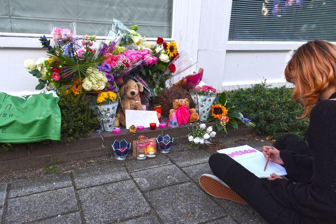 Een voormalig klasgenootje zit in stilte de bloemenzee ter nagedachtenis aan Megan te tekenen.