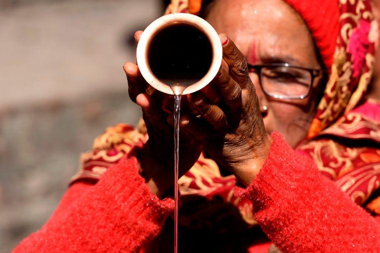 Een Hinduvrouw voert een ritueel uit tijdens de gedeeltelijke zonsverduistering in Kathmandu.