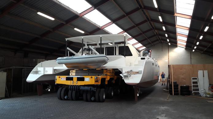 De catamaran van Paul de Preter en Jolanda van der Veen uit Helmond wordt vervoerd en gaat te water.