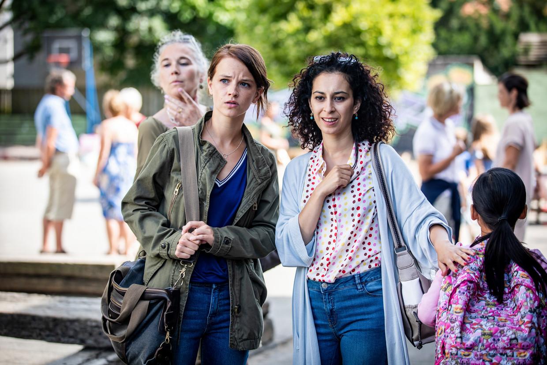 Hannah (Lynn Van Royen) en Mel (Ikram Aoulad) op het schoolplein in de Vlaamse versie van de comedy De luizenmoeder.  Beeld VTM
