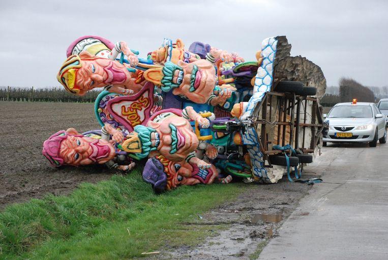 Eén van de drie wagens van de carnavalsgroep ligt op de zijkant naast de weg.