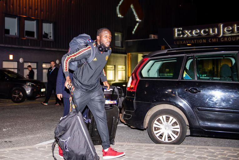 Een zwaarbeladen Romelu Lukaku wandelt naar zijn auto.
