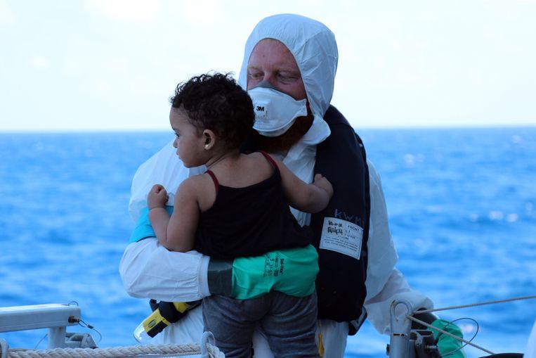 Een bemanningslid van het Nederlandse marinefregat Zr. Ms. Van Amstel brengt een kind aan boord, 14 juni 2014. Beeld ANP