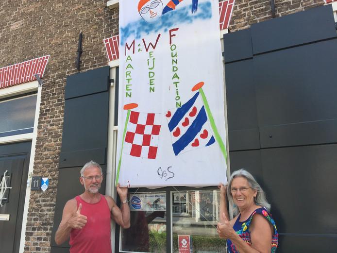 Cor Schoenmakers en Netty Revet bij hun zelfgemaakte vlag