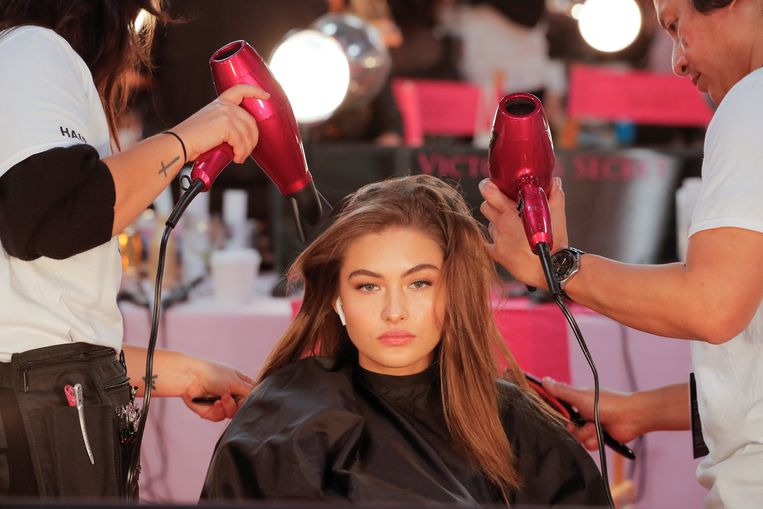 Gigi Hadid wordt backstage onder handen genomen door het beautyteam.