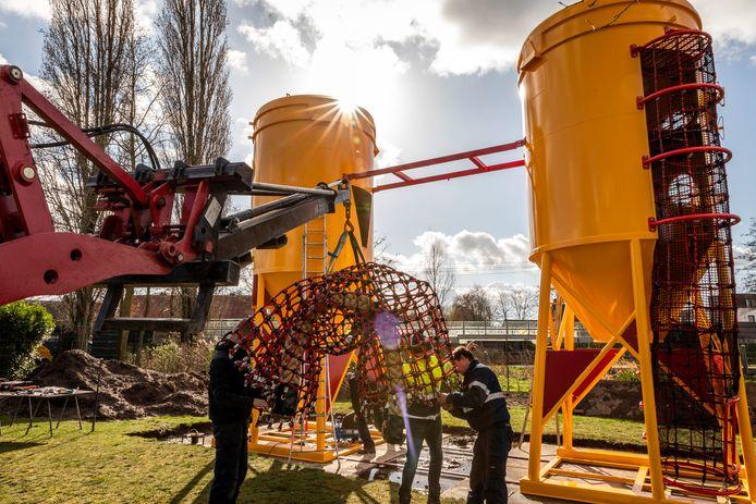 Medewerkers van speeltoestellenbouwer Nijha zijn bezig met de loopbrug die tussen de twee silo's moet komen. De omgebouwde betonsilo's vormen de basis van het nieuwe speeltoestel van Speeltuin Helmond-West.