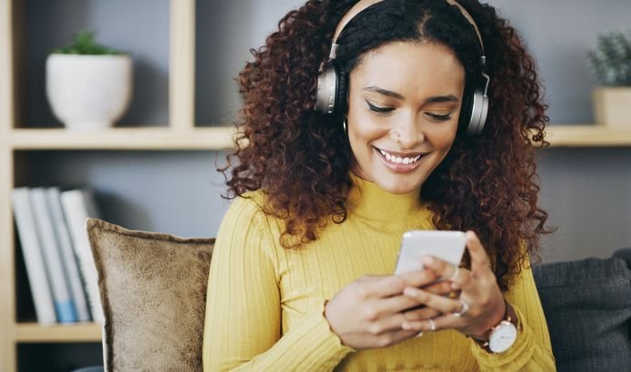 Shot of a young woman wearing headphones while using her cellphone at home