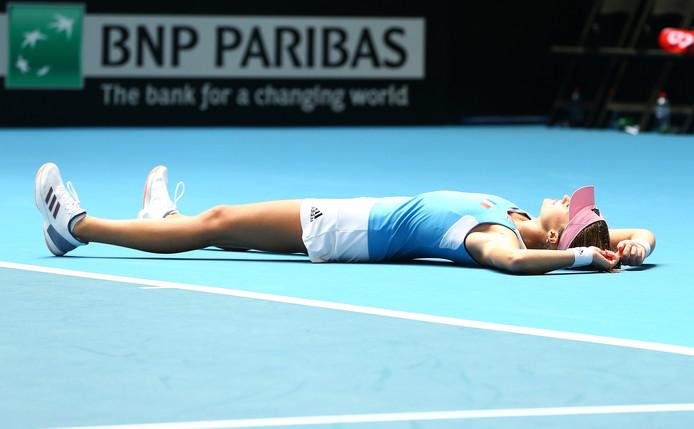 Kristina Mladenovic laat zich vallen op het hardcourt na het beslissende punt.